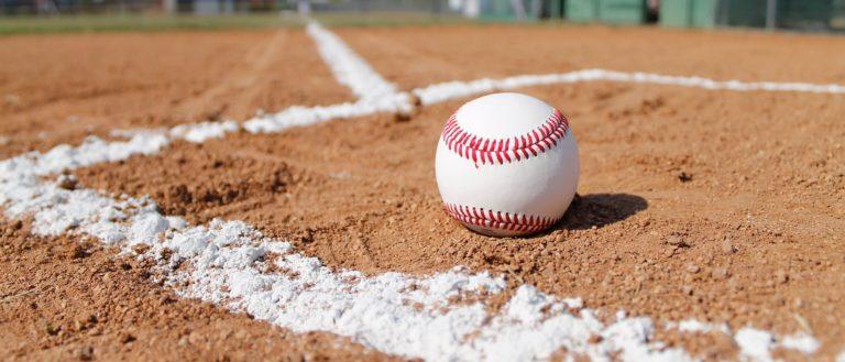 Baseball sitting inside a batter's box on a bright blue day.