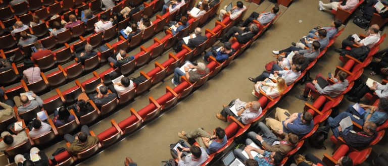 An auditorium of people watching a lecture.