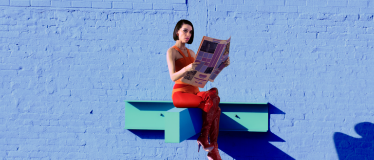 St. Vincent sitting on top of a steel beam in front of a blue background.