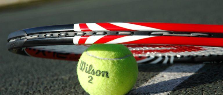 Tennis racket sitting atop a tennis ball on a court.