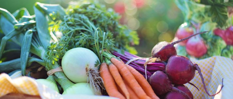 Carrots, onions, and beets in a basket.