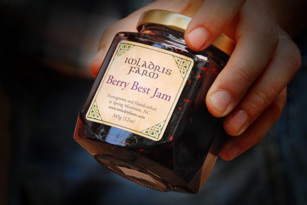 A person holding a jar of Imladris Farm Berry Best Jam.