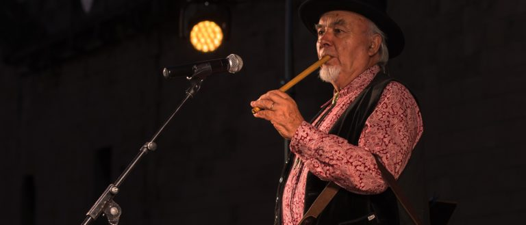 A storyteller on stage with a tambourine and fife.
