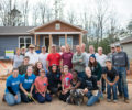 Volunteers for Asheville Area Habitat for Humanity in front of a newly built home.